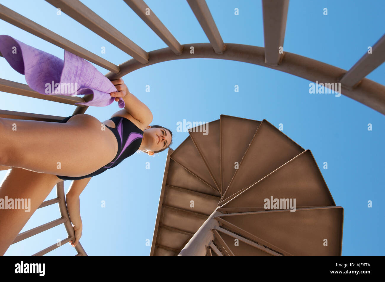 Female diver on spiral staircase to board, view from below - Stock Image