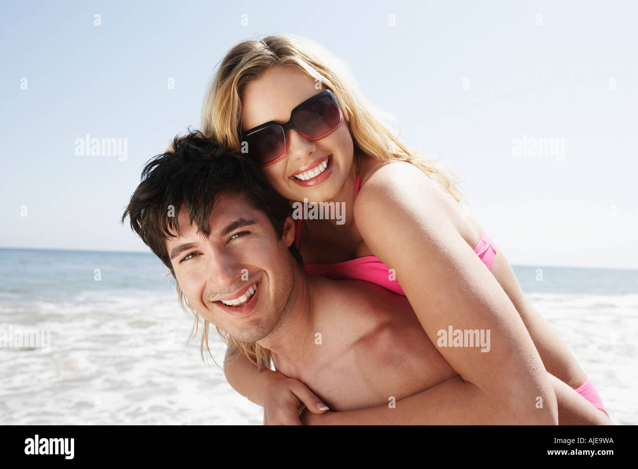 Young man with woman oh shoulders at beach, portrait - Stock Image