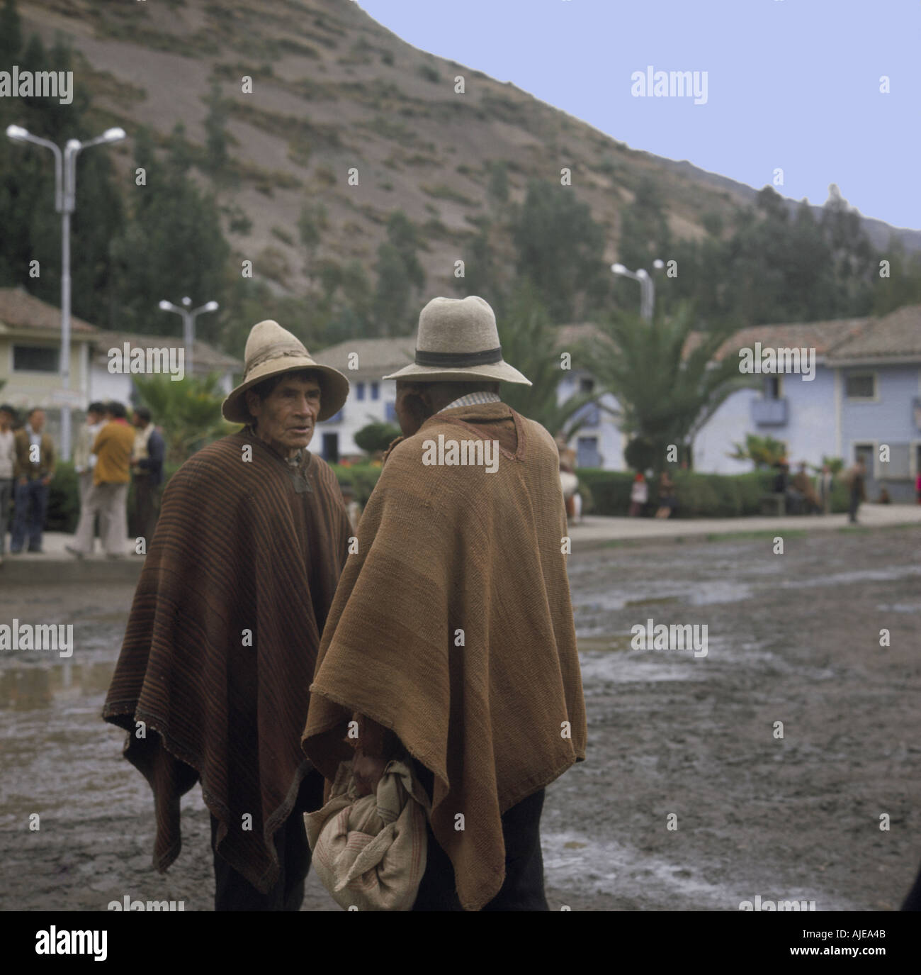 Two local men dressed in tradional homespun ponchos meet for a chat in a main square of Yungay Peru andes 1968 - Stock Image