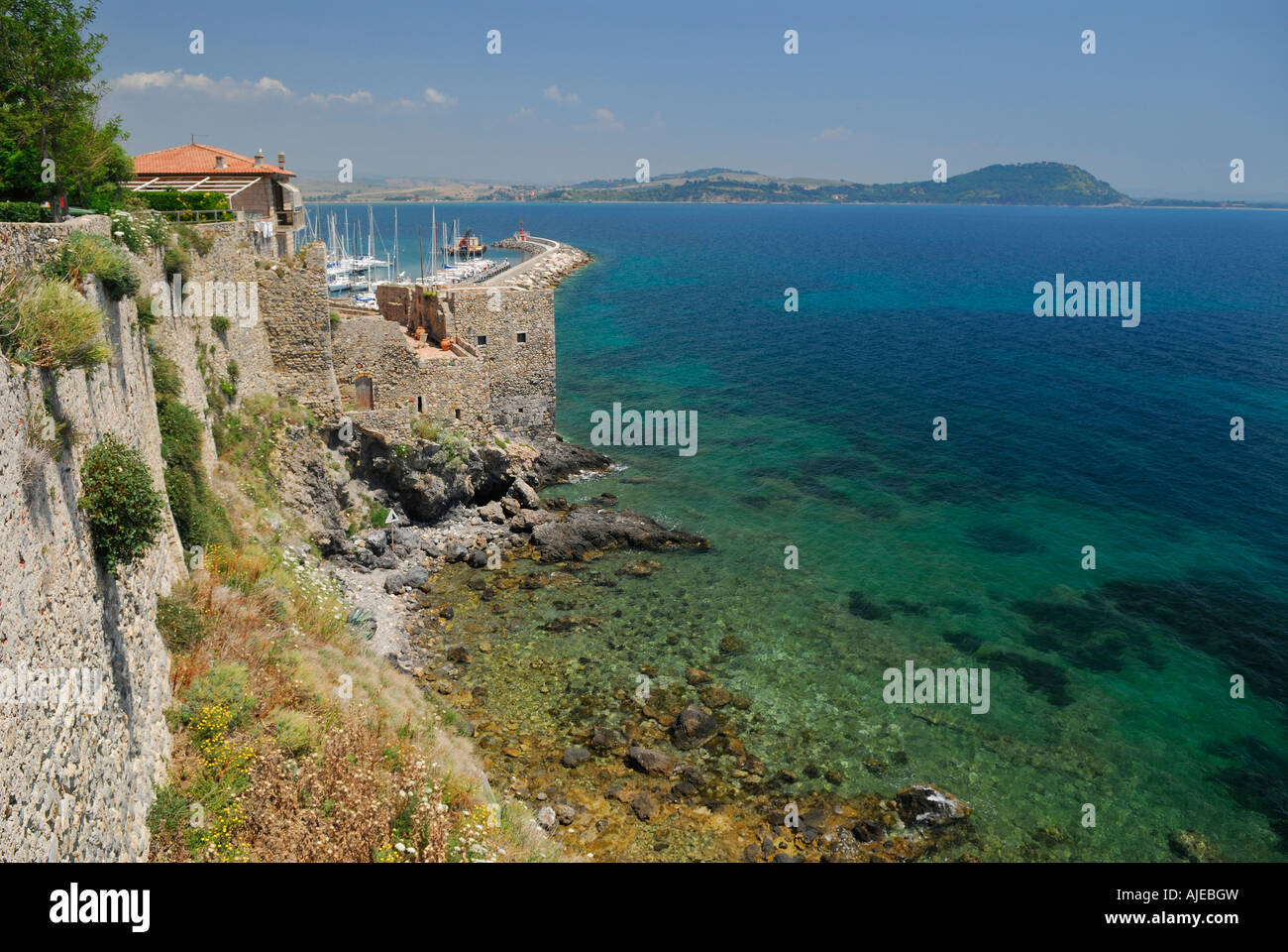 Clear blue Mediterranean sea and cliff high stone walls of Talamone Italy - Stock Image