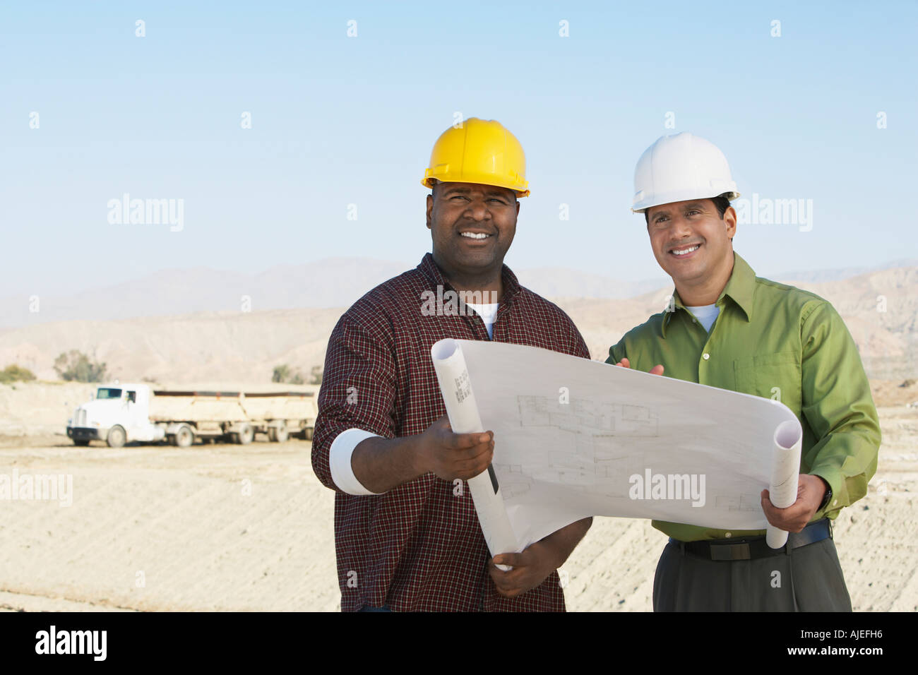 Construction Workers wearing hard hats, looking at plan on Site - Stock Image