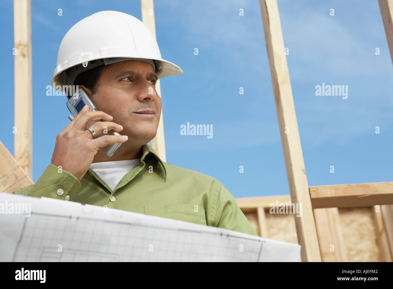 Construction Worker wearing hard hat, Using Cell Phone on construction site - Stock Image