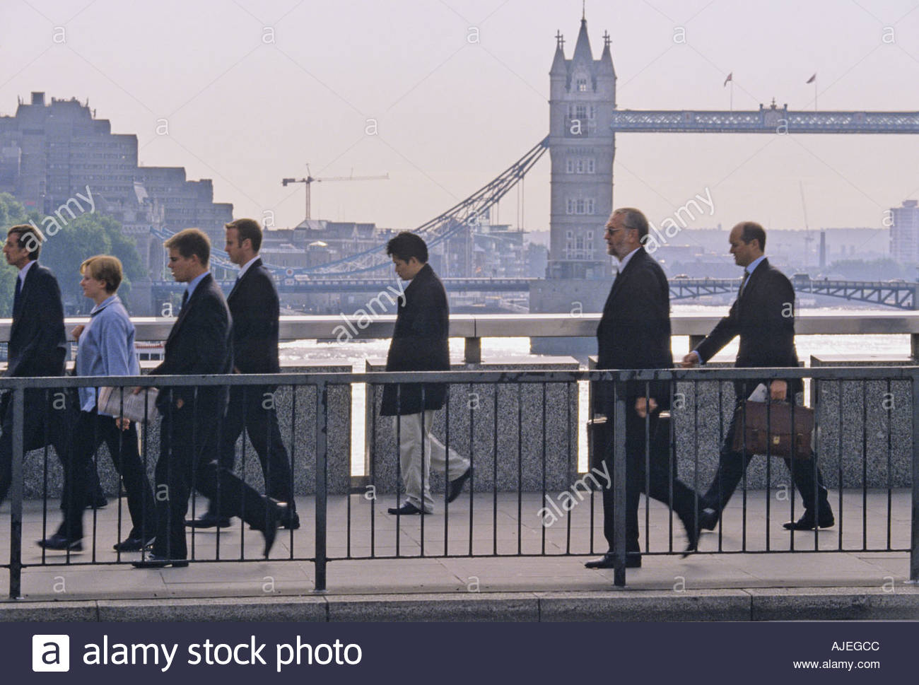 Commuters walk over London Bridge in the morning going to work in the City; Tower Bridge in the background - Stock Image
