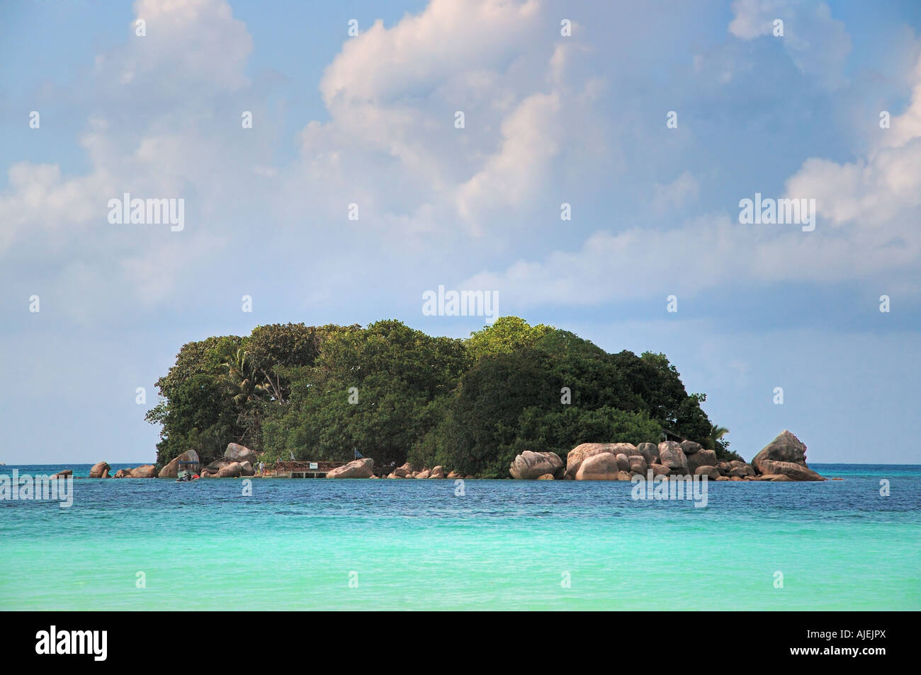 Tiny island covered in lush tropical vegetation Stock Photo