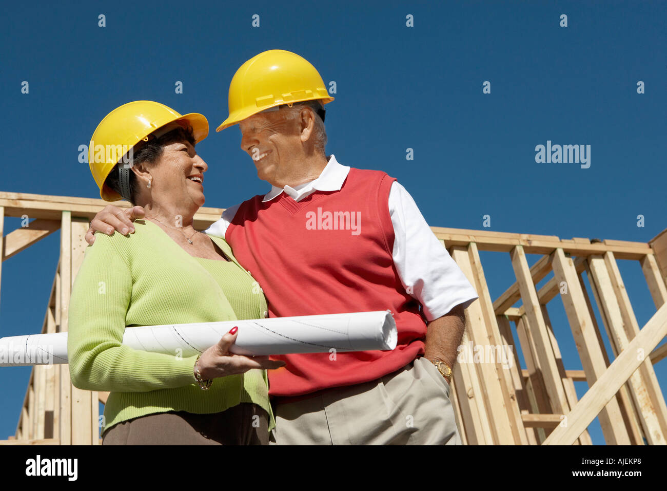 Couple in front of house being built, half-length - Stock Image
