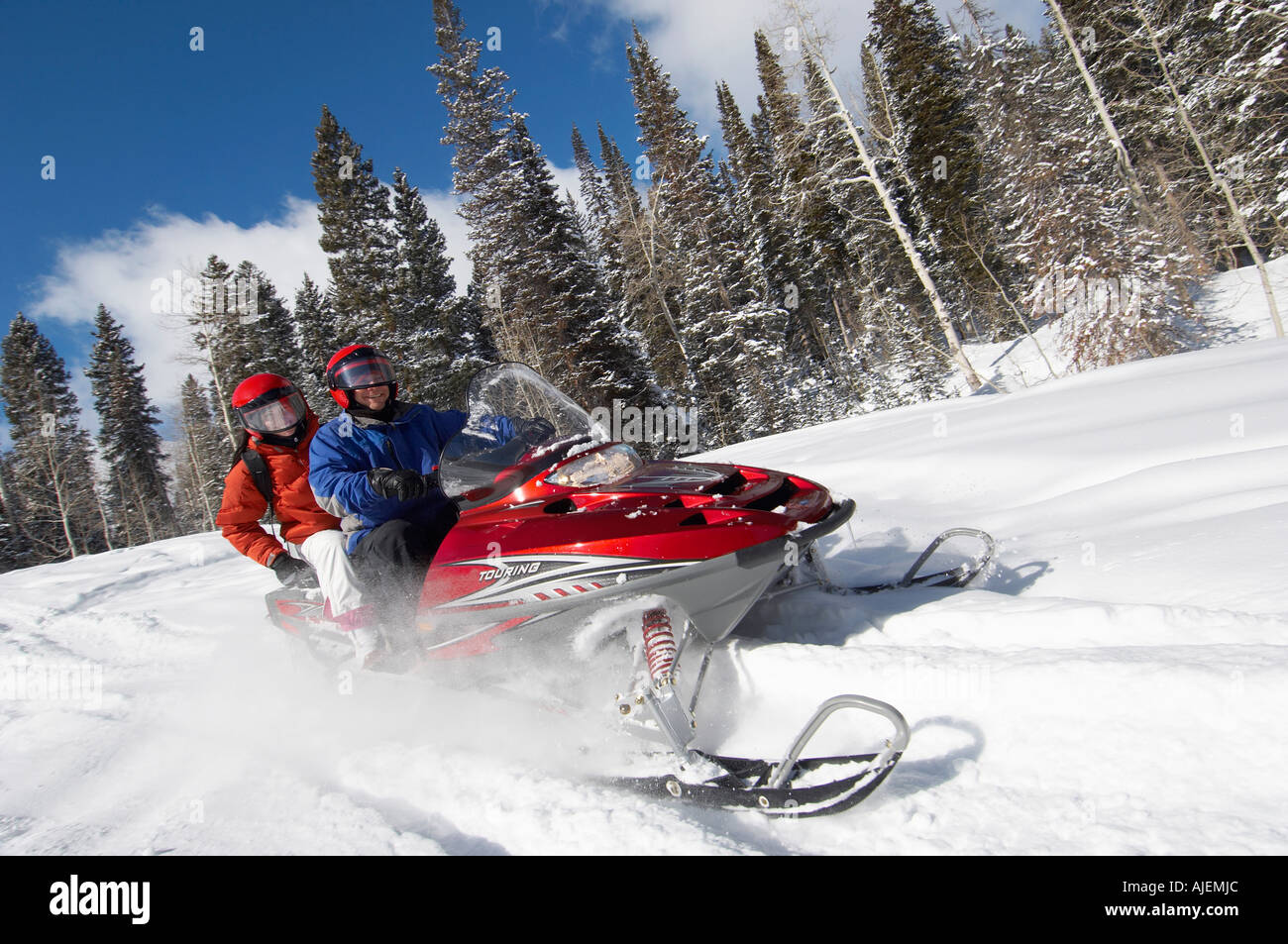 Couple driving snowmobile through snow - Stock Image