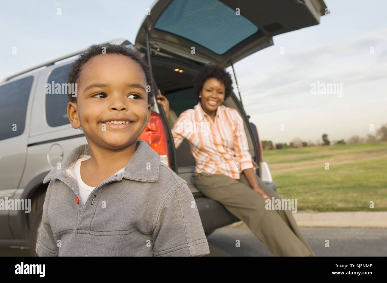 Young boy and mother by open car boot - Stock Image