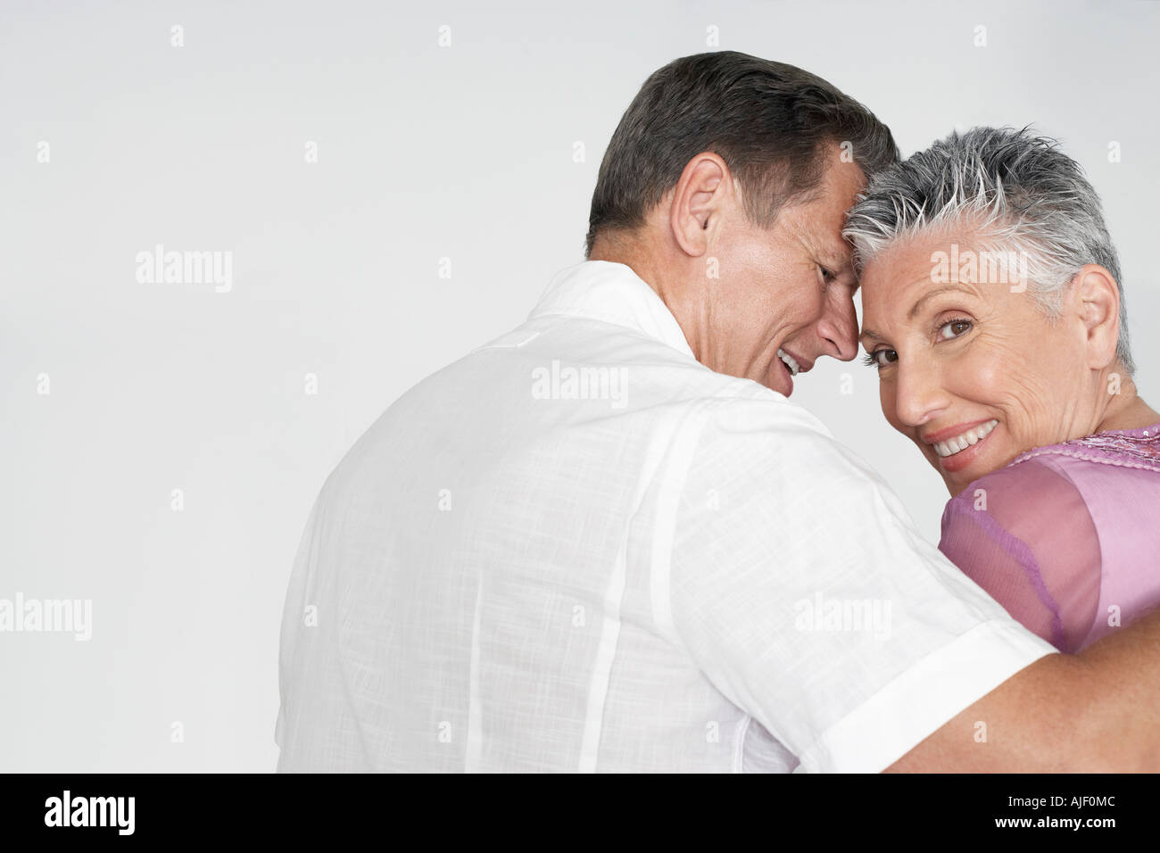 Couple embracing against white background, portrait - Stock Image