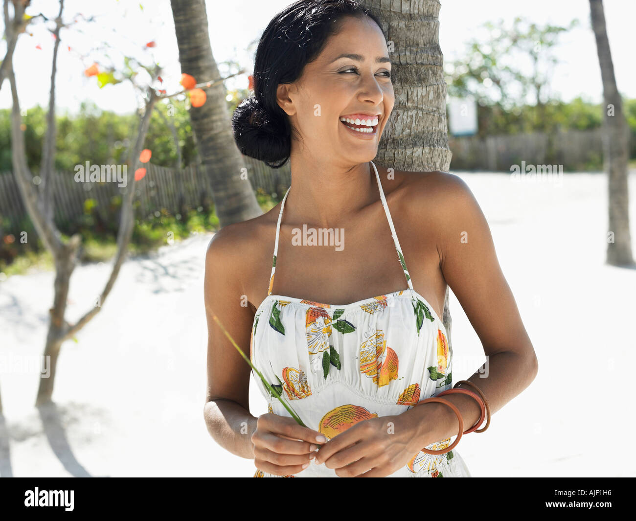 Woman leaning against palm tree on beach, half-length Stock Photo