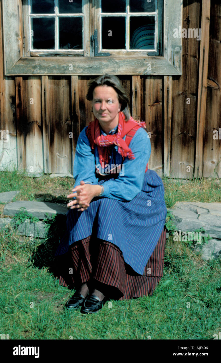 Woman in traditional dress sitting outside a timber building at a folk museum, Norway. - Stock Image