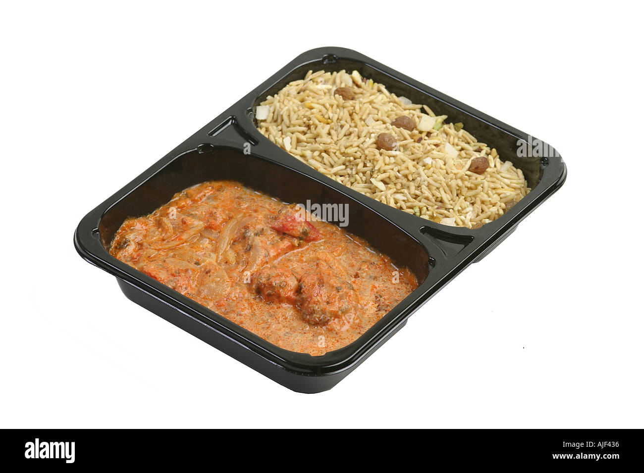 Microwaved curry in a plastic tray om a white background - Stock Image