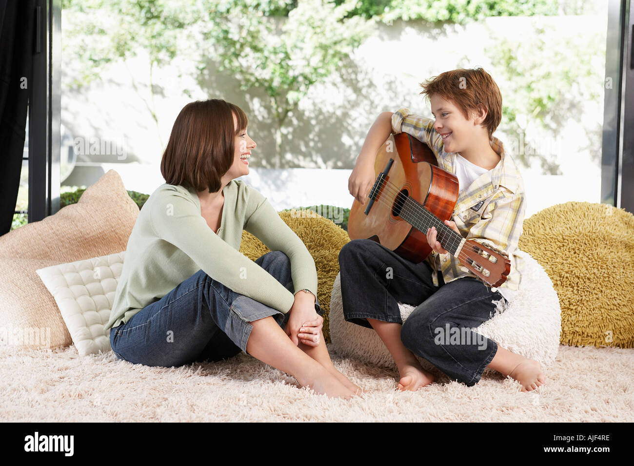 Mother listening to son play guitar - Stock Image