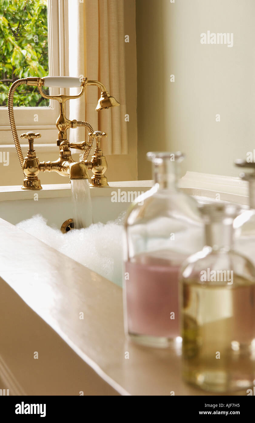 Bottles of Bath Oils on edge of bathtub filled with bubbles, water ...