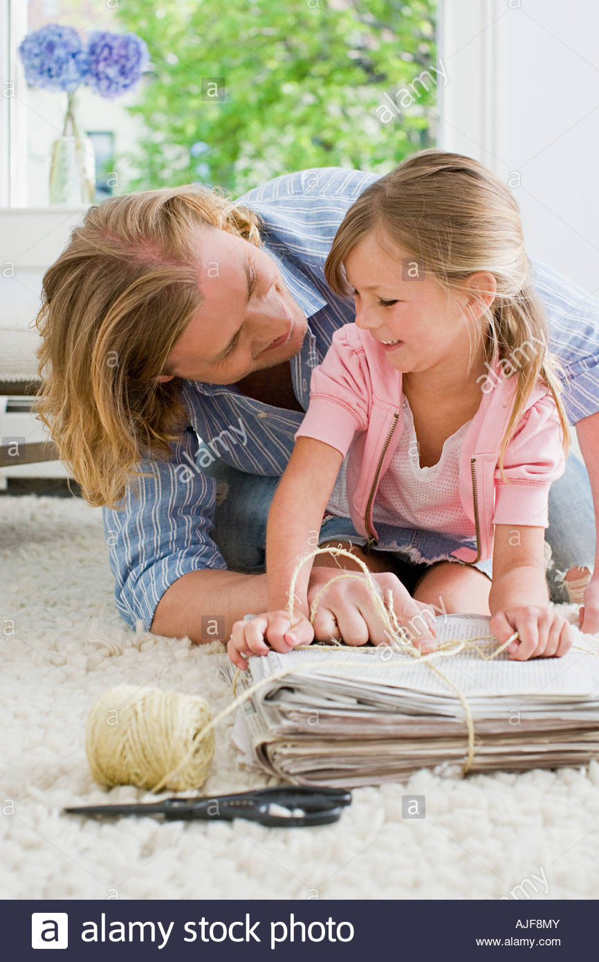 A daughter helping her father recycle - Stock Image