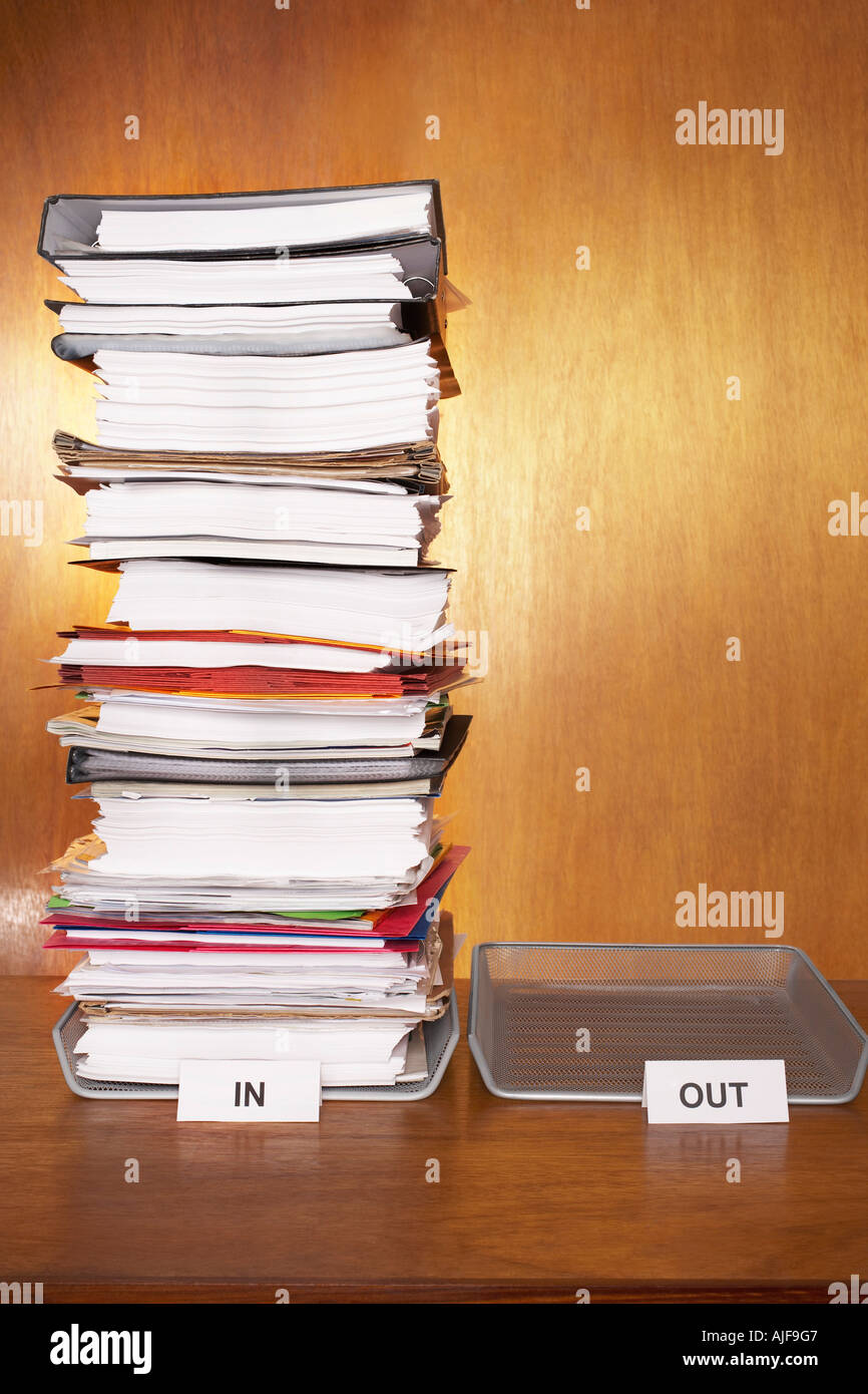 Inbox with stack of paperwork, empty outbox on desk - Stock Image