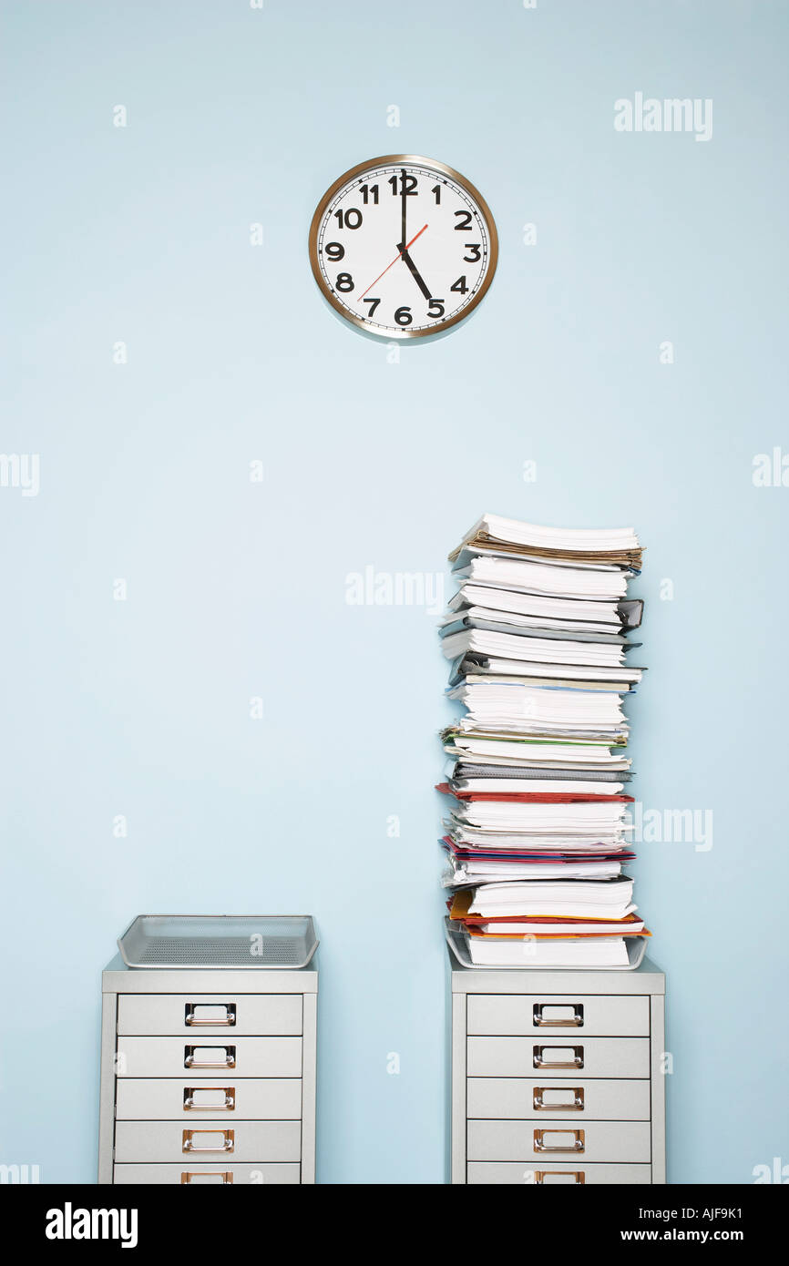 Office wall with clock, stack of paperwork in outbox on file cabinet - Stock Image