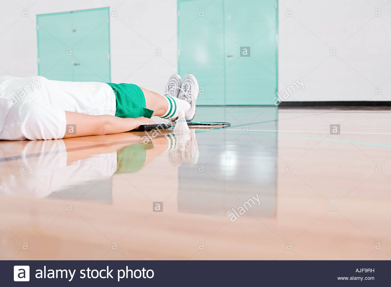 A person lying down on a badminton court... - Stock Image