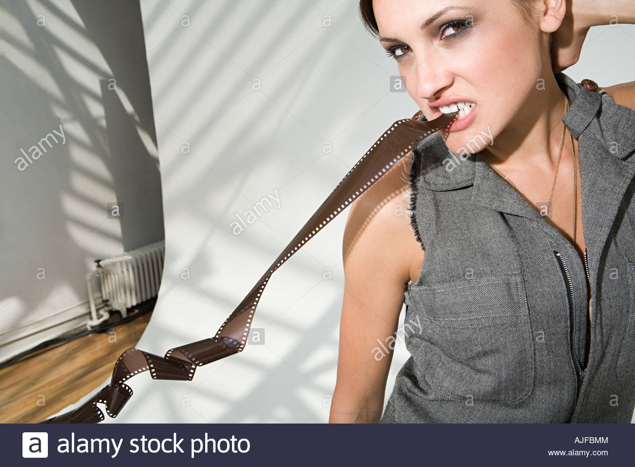 Woman biting on photographic film - Stock Image