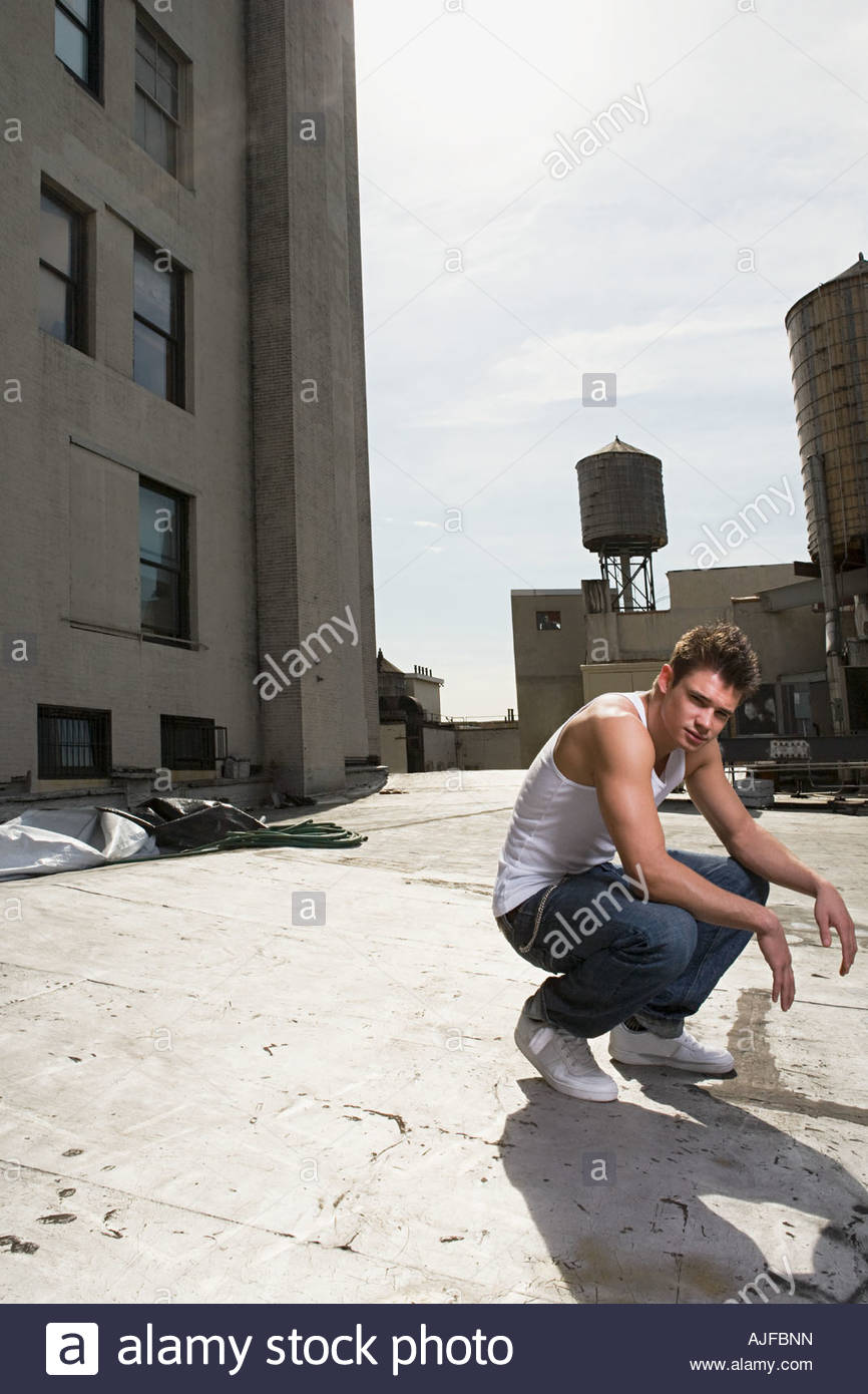 A young man crouching - Stock Image