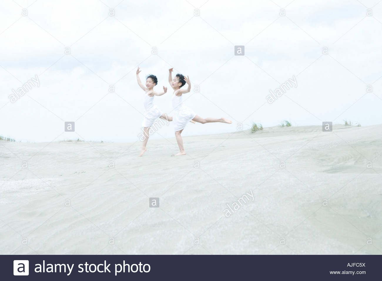 Girls dancing on beach - Stock Image
