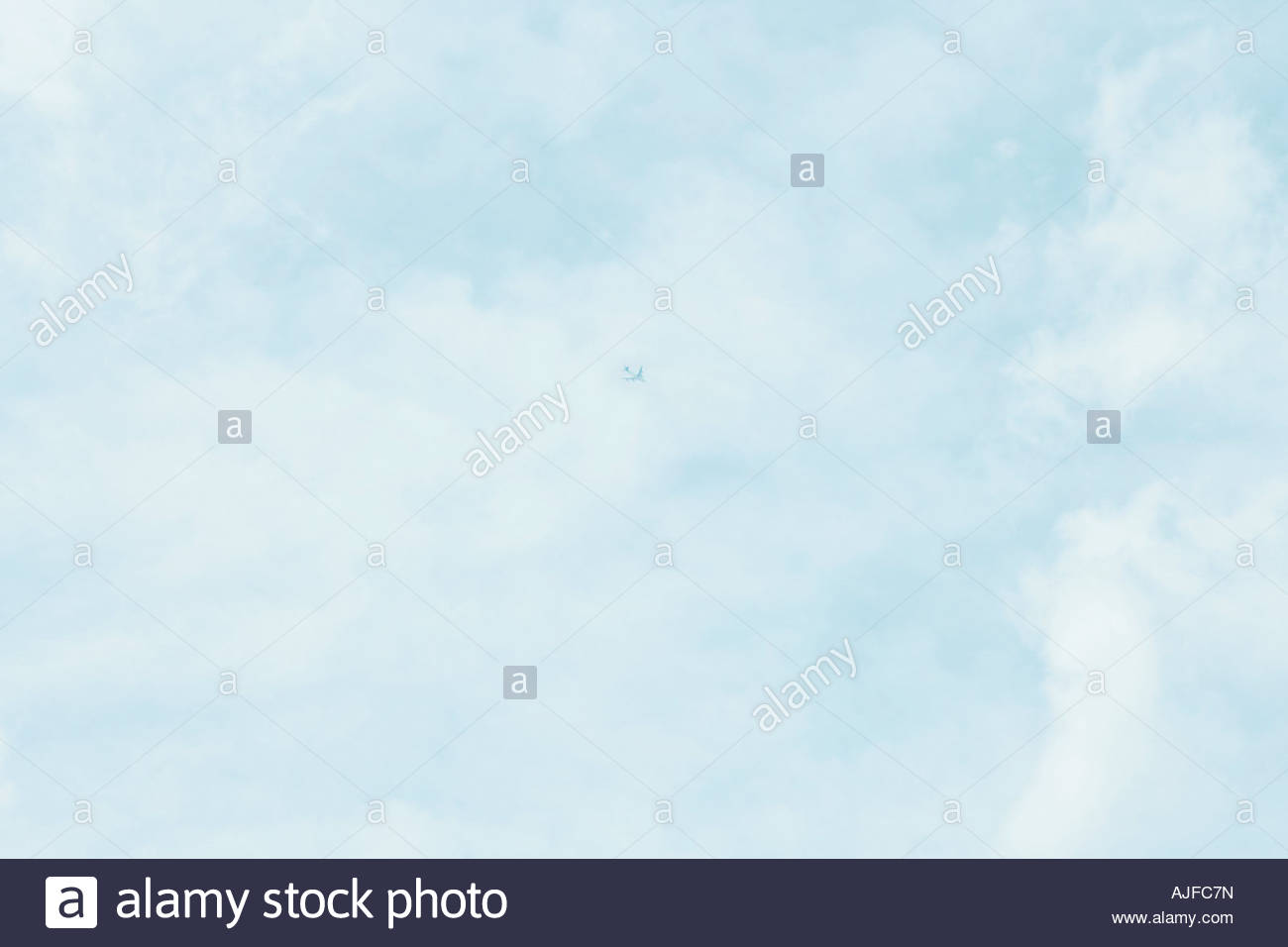 Airplane in cloudy sky - Stock Image