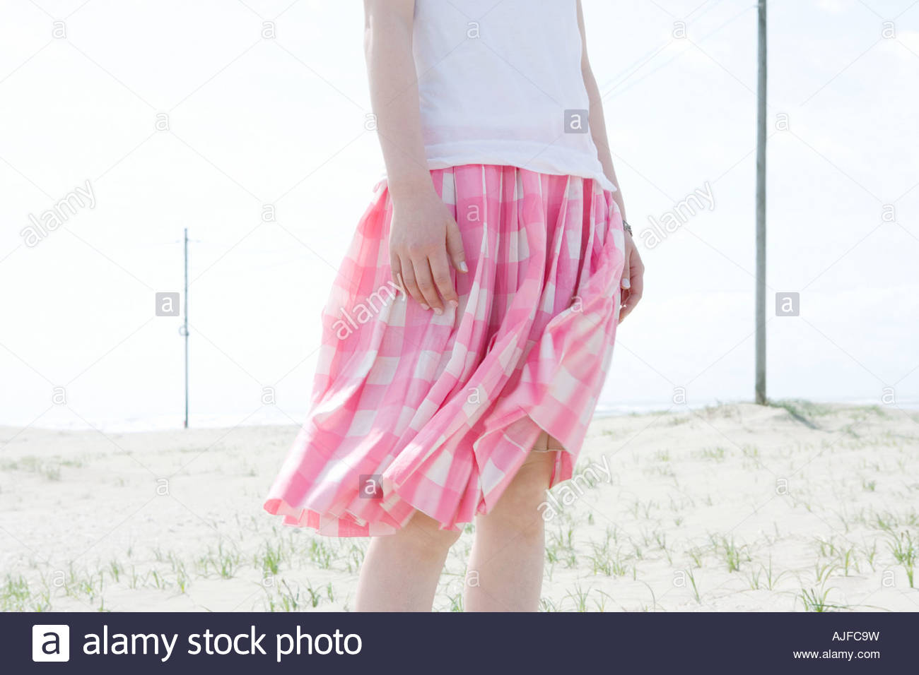 Woman with skirt blowing in breeze - Stock Image