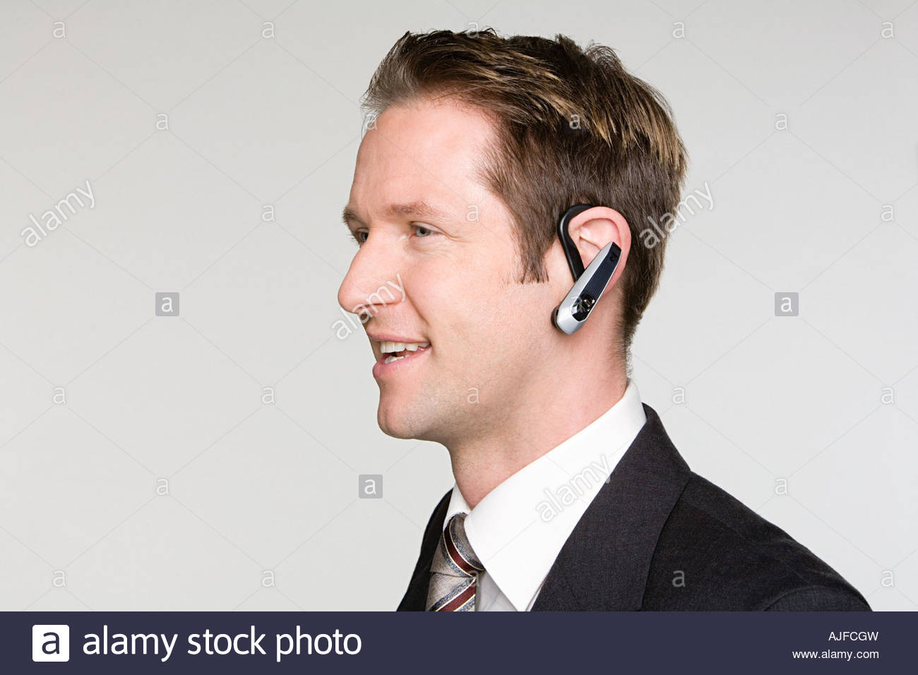 Businessman using hands free device - Stock Image