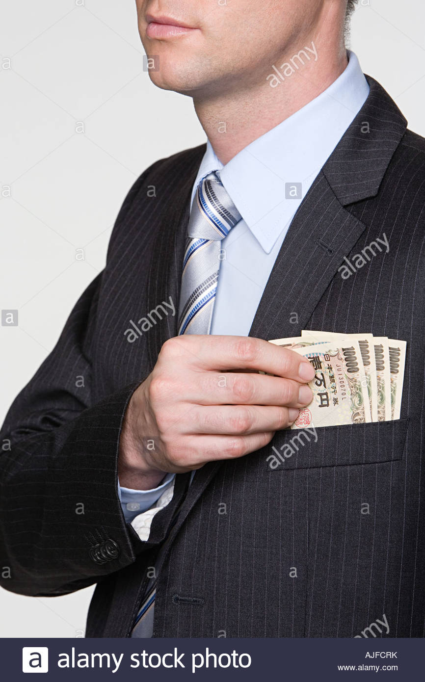 Man with yen notes in his pocket - Stock Image