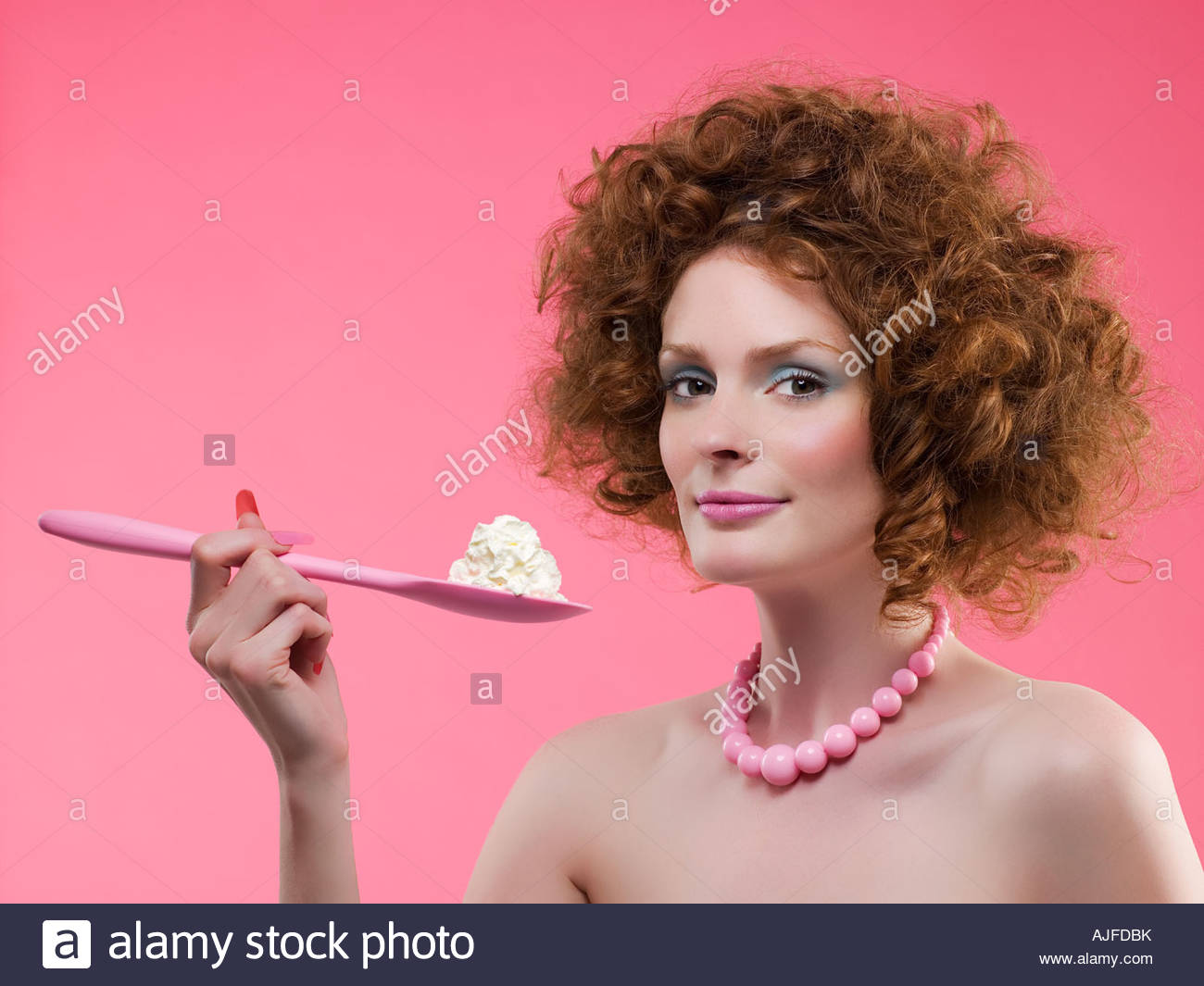 Woman holding cream on a spoon - Stock Image