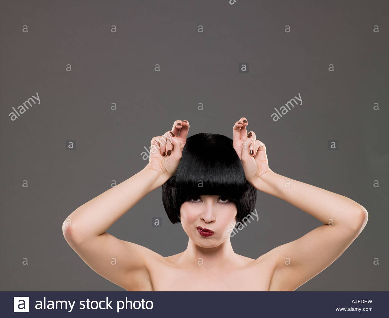 Woman grimacing and making hand gestures - Stock Image