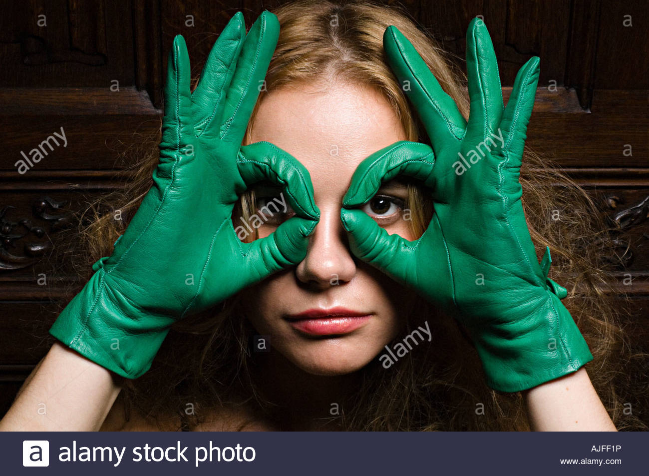 Woman looking through fingers in green gloves - Stock Image