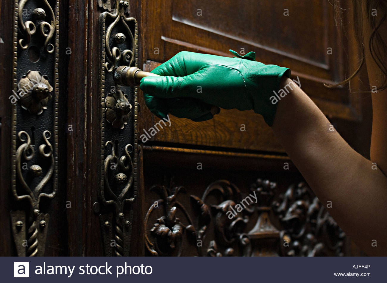 Woman opening a carved wooden door - Stock Image