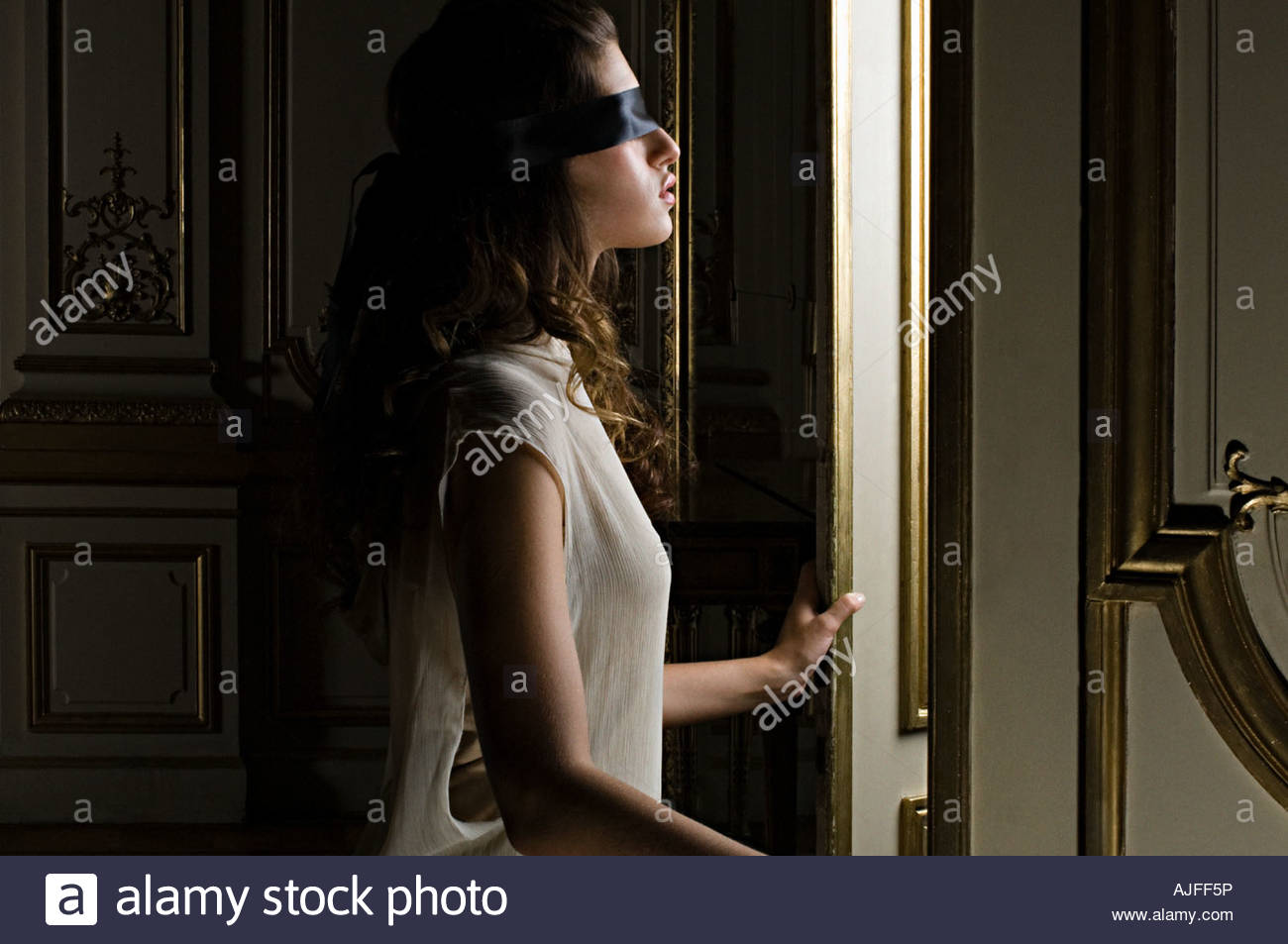 Blindfolded woman opening door - Stock Image