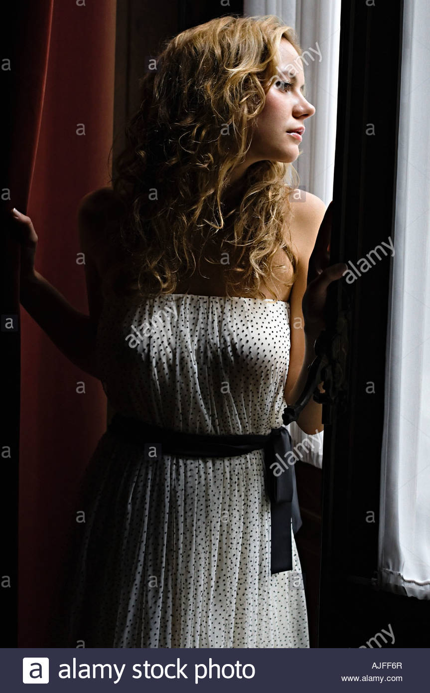 Woman looking though a window - Stock Image
