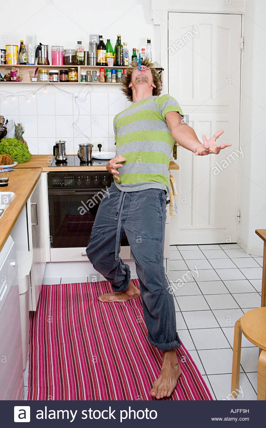 Man playing air guitar in kitchen - Stock Image