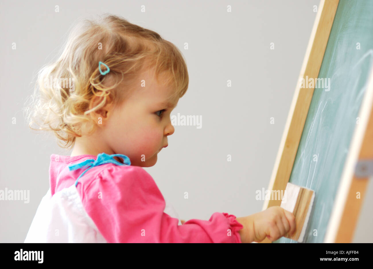 Two year old girl erasing a chalk board - Stock Image