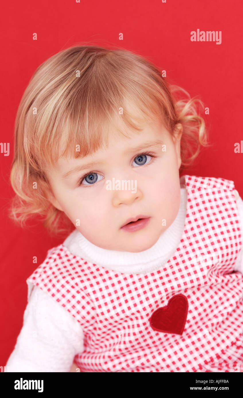 Two year old girl with heart on dress - Stock Image