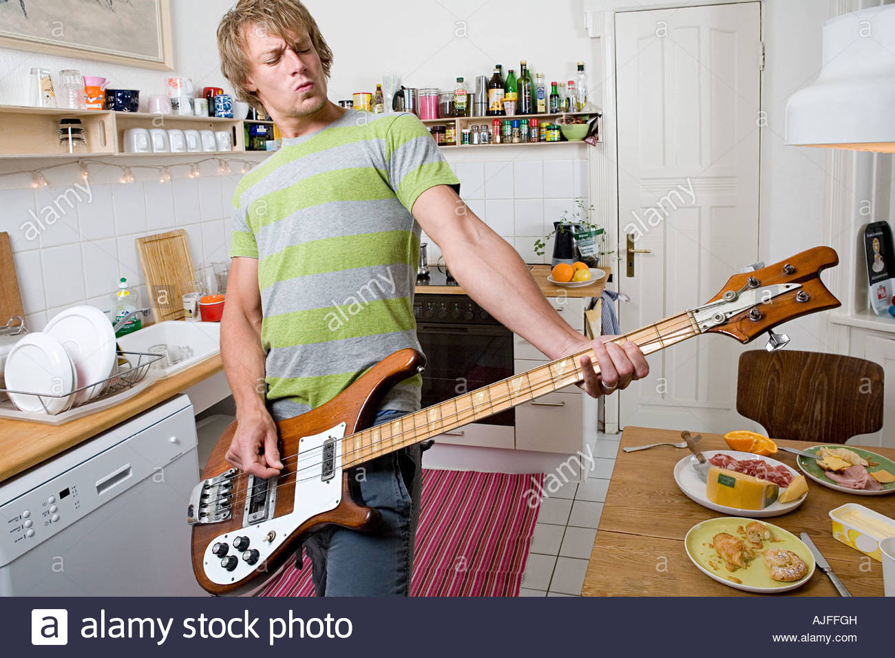 Man playing guitar in kitchen - Stock Image