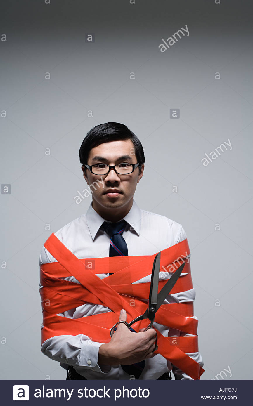 An office worker tied up in red tape - Stock Image