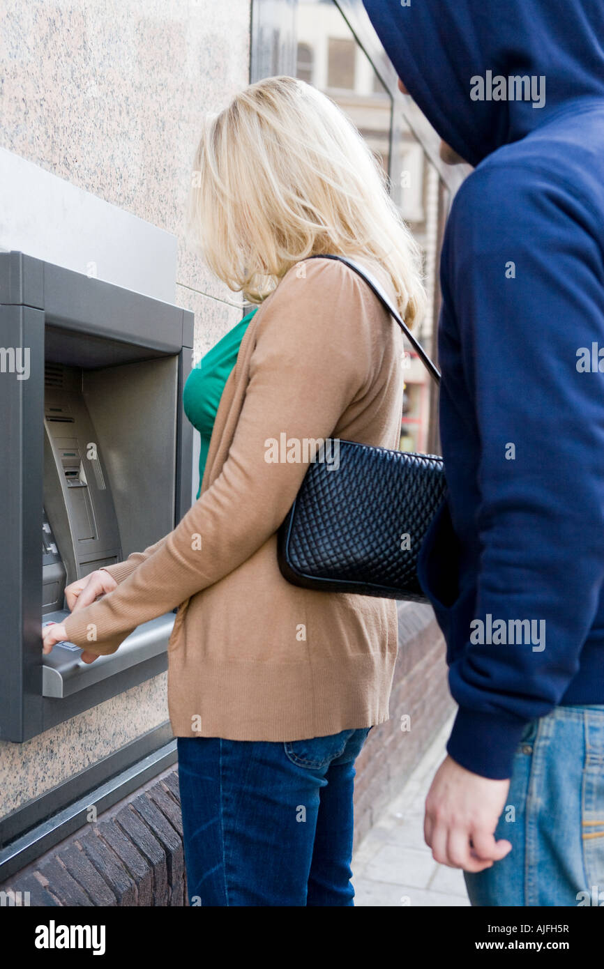 Thief looking over womans shoulder at cash machine Stock Photo