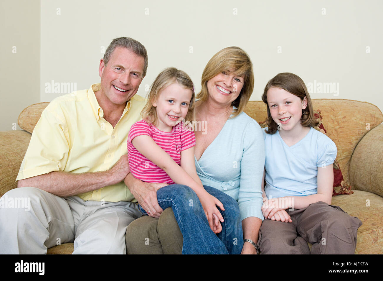 Family sitting on a sofa - Stock Image