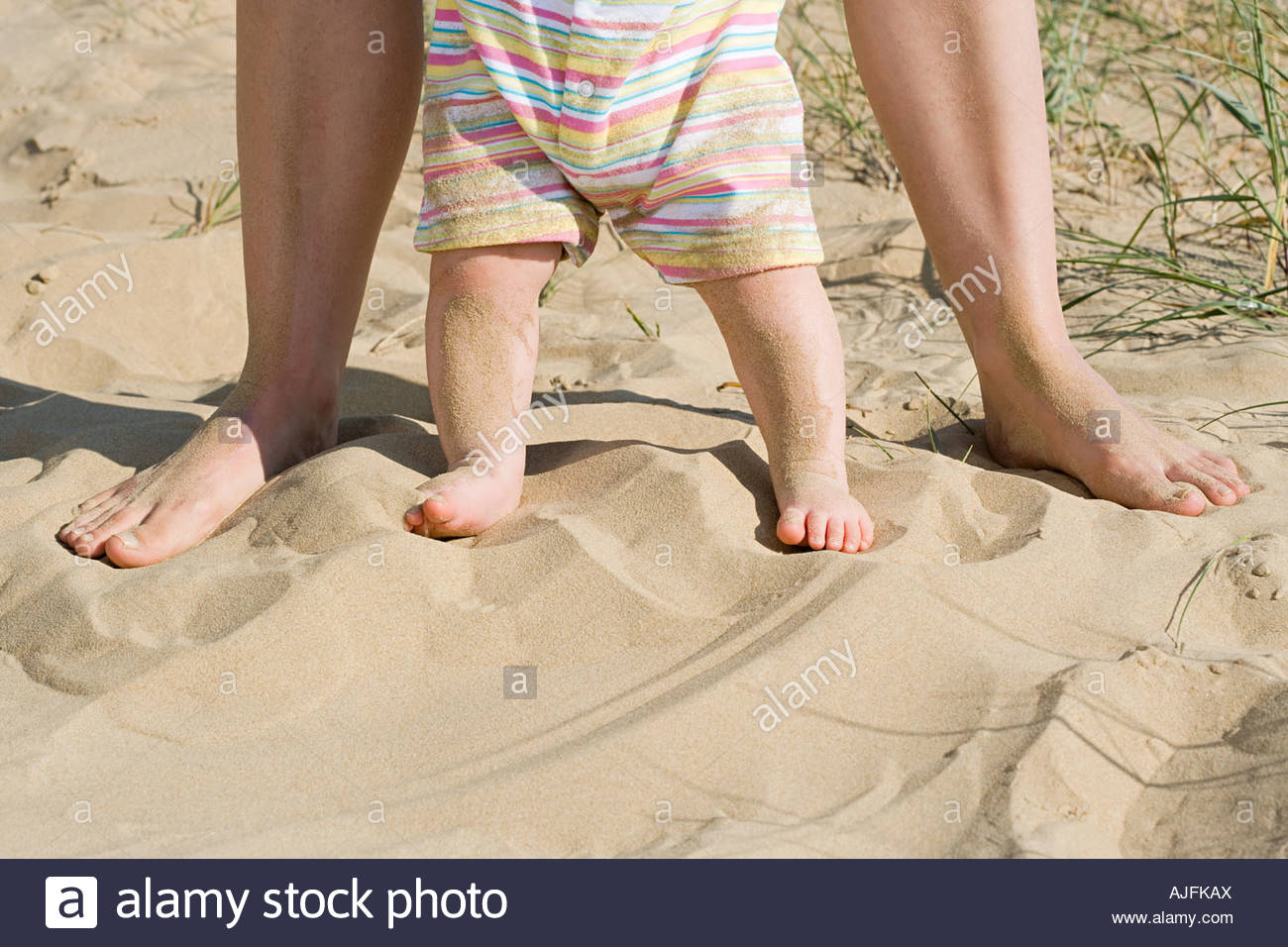 A babys legs and an adults legs - Stock Image