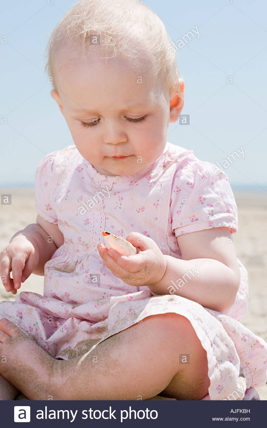 Baby girl holding a seashell - Stock Image