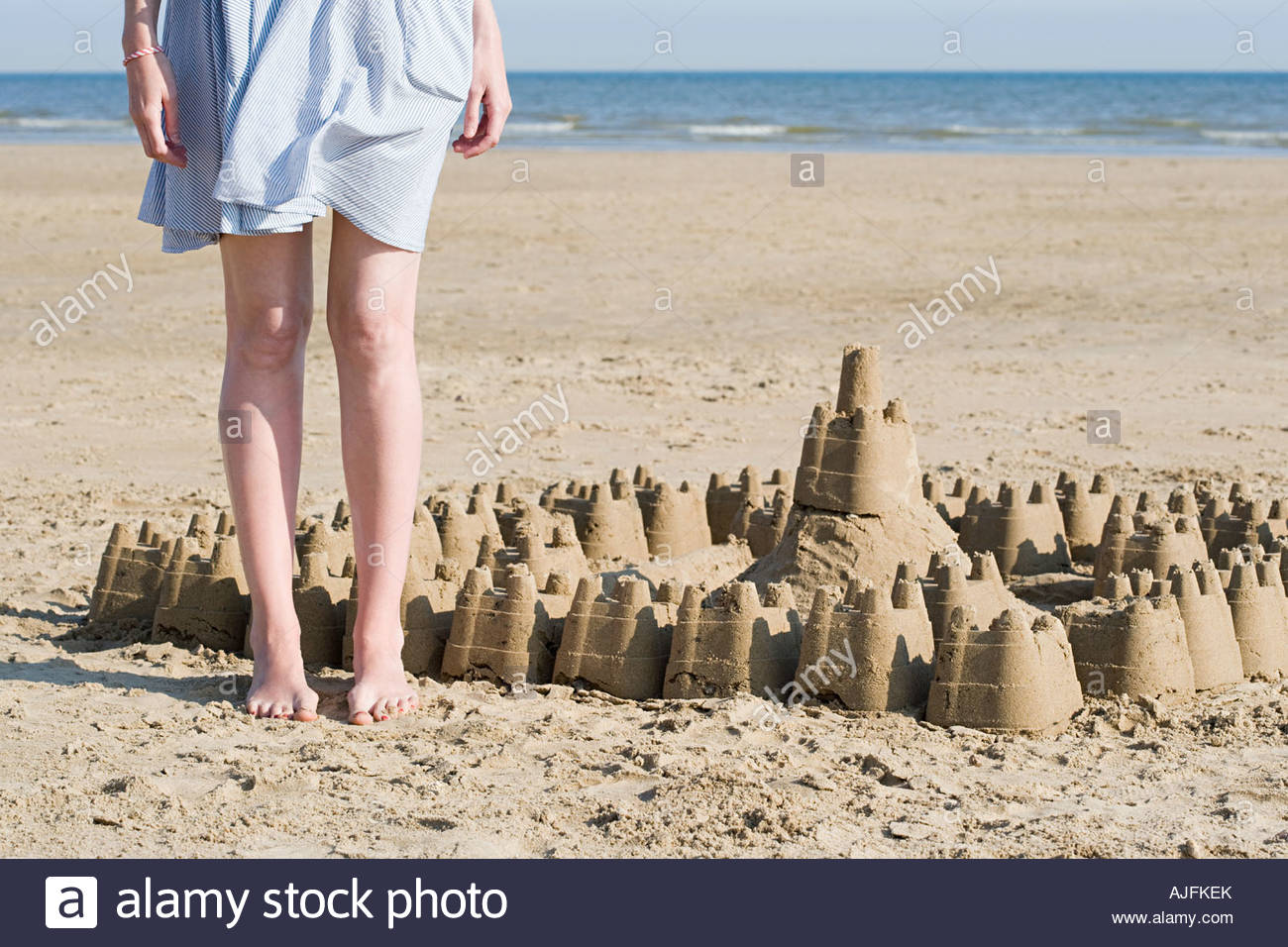 Woman stood next sandcastle - Stock Image