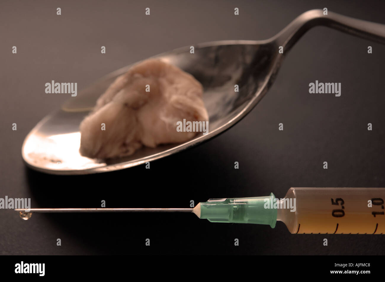 heroin in a hypodermic needle after being cooked on a spoon - Stock Image