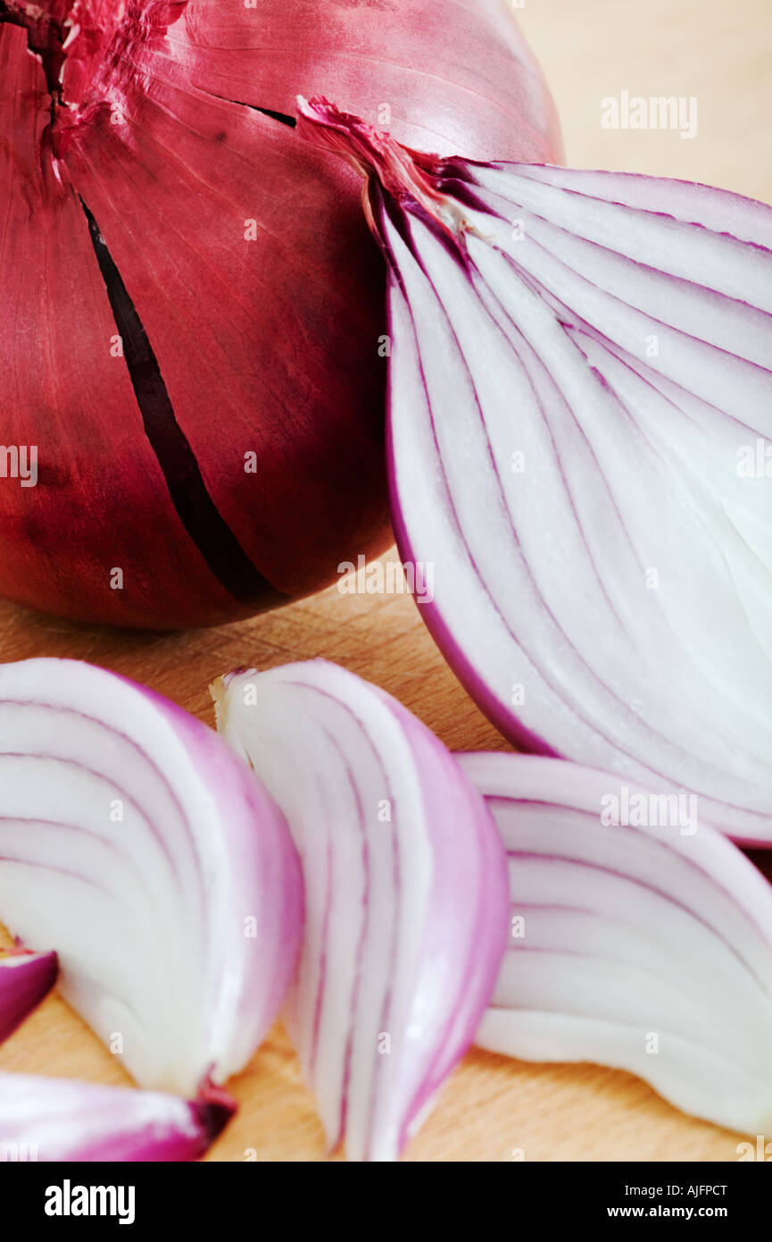 Red onions on wooden cutting board Studio shot against white background - Stock Image