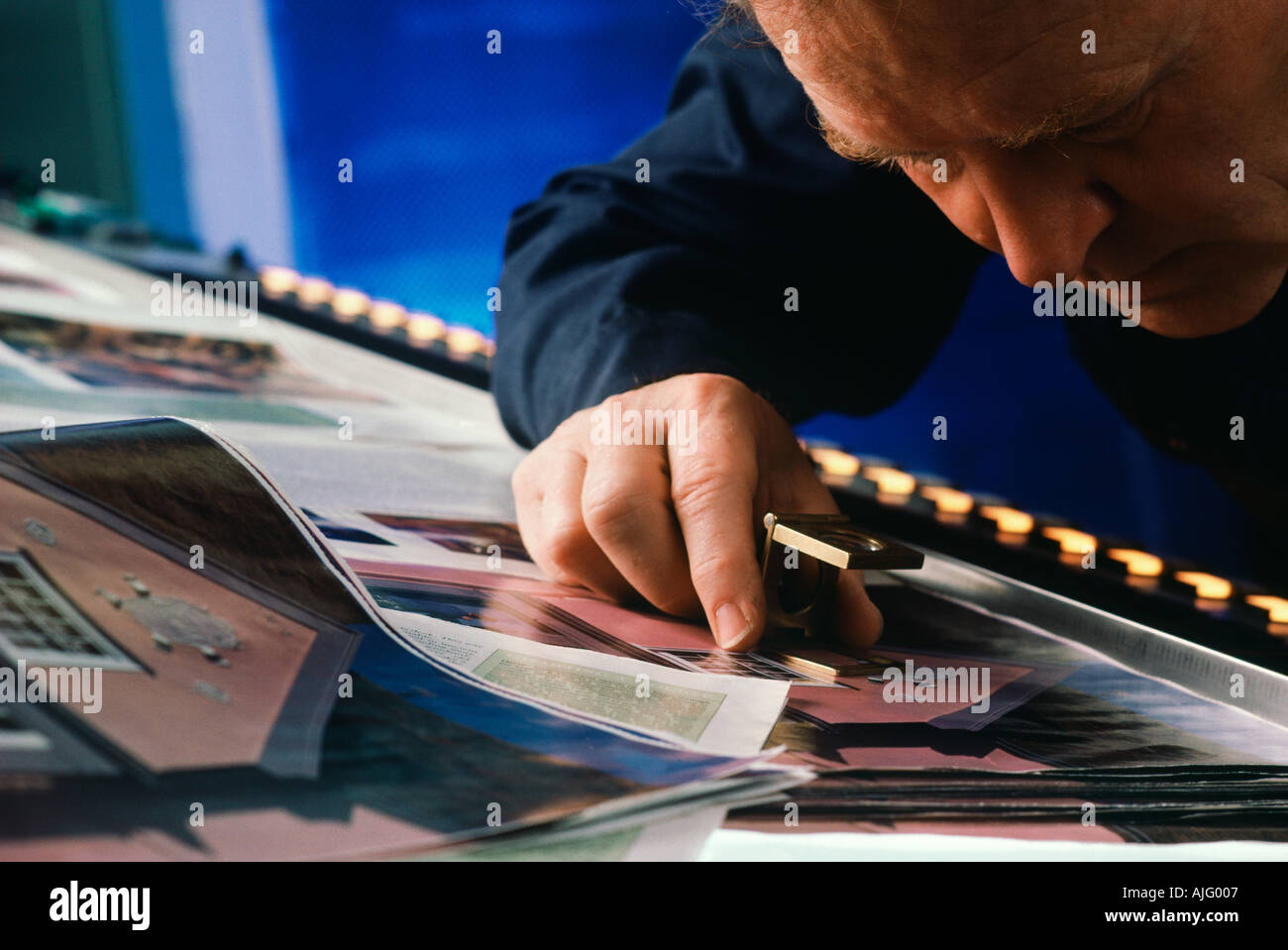 Caucasian pressman checking Proof sheet color with loupe in printing plant - Stock Image