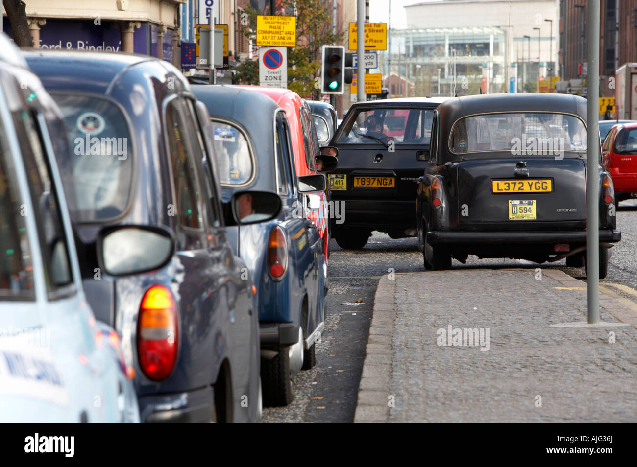 taxi leaving front of taxi rank with row of london style hackney carriage taxis lined up in Belfast City Centre - Stock Image