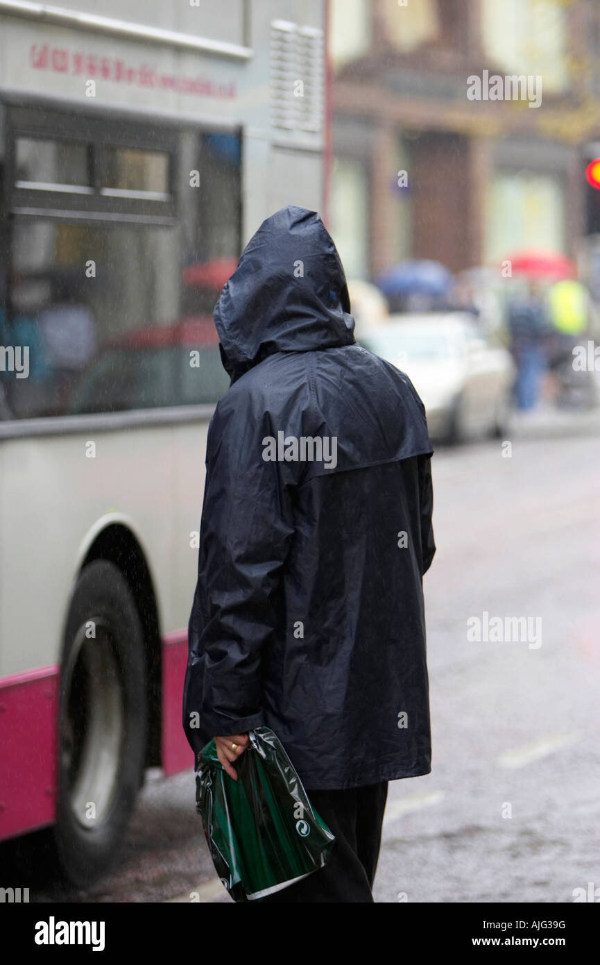 married man in blue raincoat holding plastic bag stands at the side of the road in the rain waiting for a bus to - Stock Image