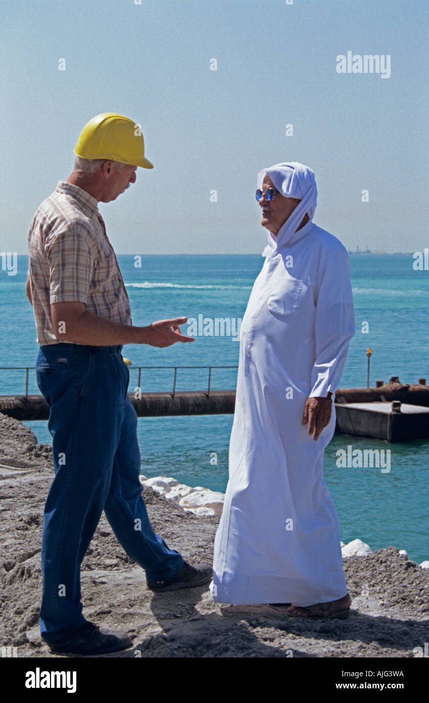 European project manager talking to a member of local Arab Community Bahrain. - Stock Image